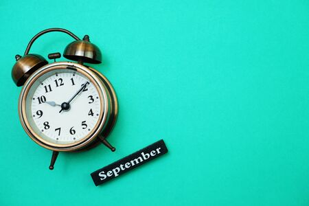Alarm clock and September calendar with space copy on green mint background