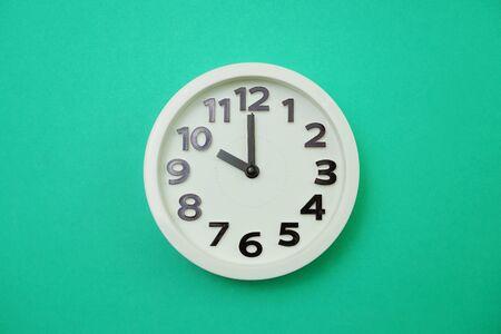 White round clock showing Ten oclock on green background Banco de Imagens