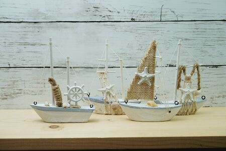 Nautical background with Sailboat Model on wooden background Фото со стока