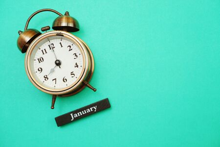 Alarm clock and January calendar with space copy on green mint background