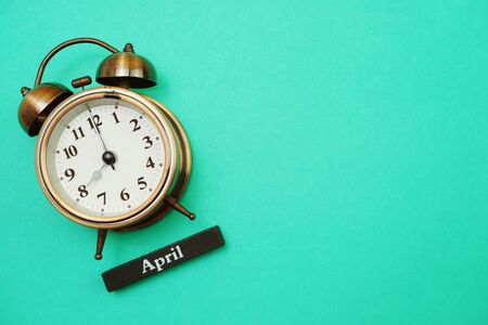 Alarm clock and April calendar with space copy on green mint background