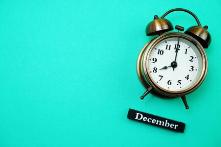 Alarm clock and December calendar with space copy on green mint background