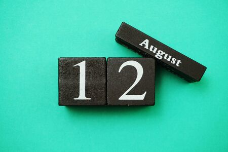 August 12th wooden calendar with space copy on green mint background