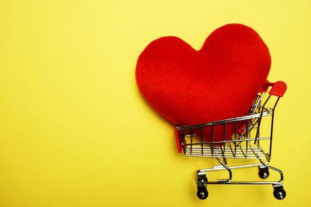 Rotes Herz und Mini-Trolley-Einkaufswagen auf gelbem Hintergrund Standard-Bild