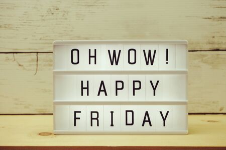 Happy Friday text in light box with space copy on wooden background