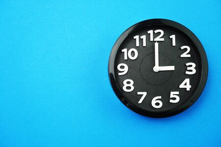 black round clock showing five o'clock on blue background