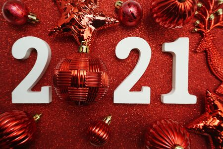 2021 with Christmas ball decoration Flat lay on red glitter background Stock Photo