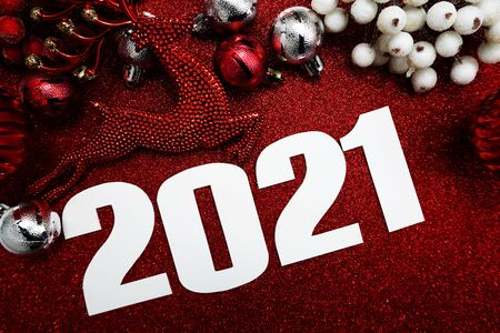 Happy New Year 2021 Decoration with Christmas ornament Flat lay on red glitter background