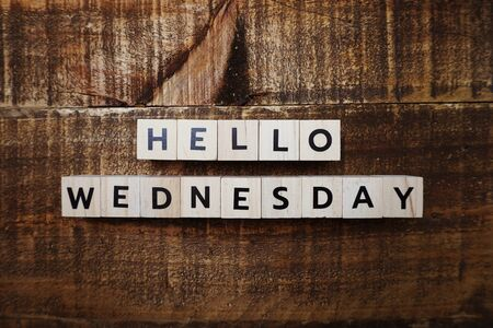 Hello Wednesday alphabet letter with space copy on wooden background