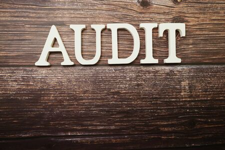Audit alphabet letters on wooden background