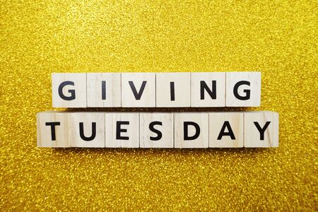 Giving Tuesday alphabet letter on yellow glitter background Foto de archivo