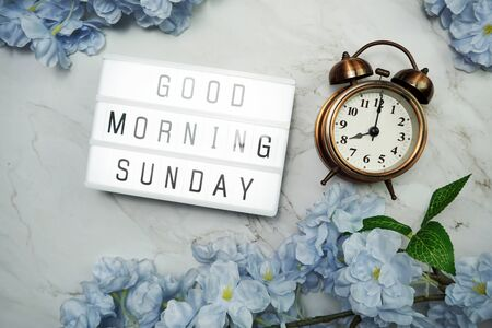 Good Morning Sunday word in light box with Flowers Decoration on wooden background Banque d'images