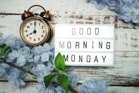 Good Morning Monday word in light box with alarm clock and Flowers Decoration on wooden background Banque d'images