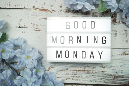 Good Morning Monday word in light box with Flowers Decoration on wooden background
