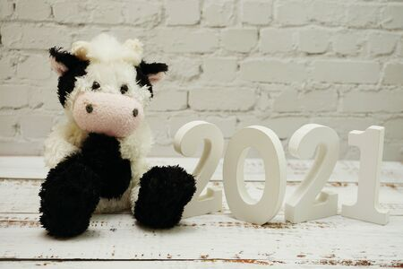 2021 Happy New Year and Cute Funny cow doll with space copy on white brick wall and wooden background