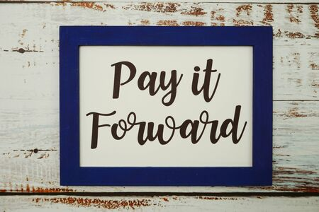 Pay It Forward written with blue photo frame flat lay on wooden background