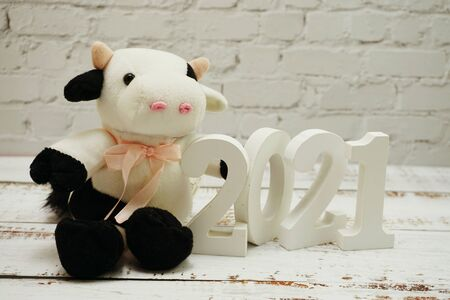 2021 Happy New Year and Cute Funny cow doll with space copy on white brick wall and wooden background Фото со стока