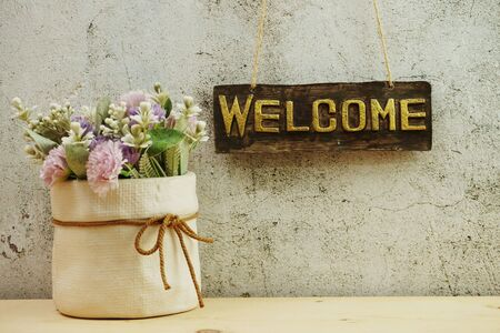 Welcome sign Hanging on grunge cement wall background Banco de Imagens - 150086498
