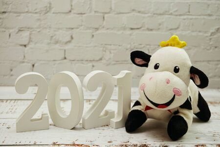 2021 Happy New Year and Cute Funny cow doll with space copy on white brick wall and wooden background Imagens