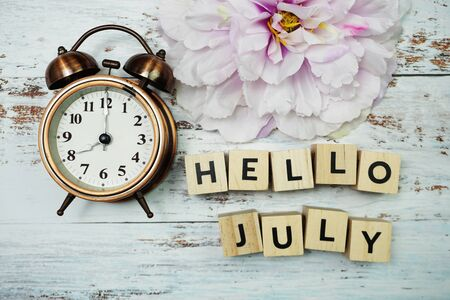 Hello July with alarm clock on wooden background Фото со стока