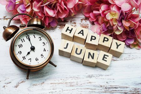 Happy June alphabet letter with alarm clock on wooden background