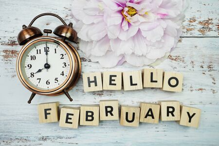 Hello February alphabet letters with alarm clock on wooden background