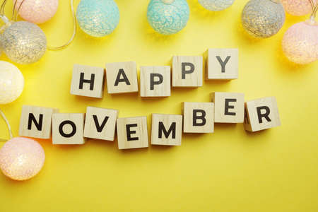 Happy November alphabet letter with LED Cotton ball Decoration on yellow background