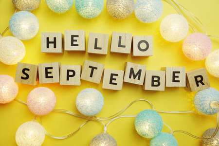 Hello September alphabet letter with LED Cotton ball Decoration on yellow background