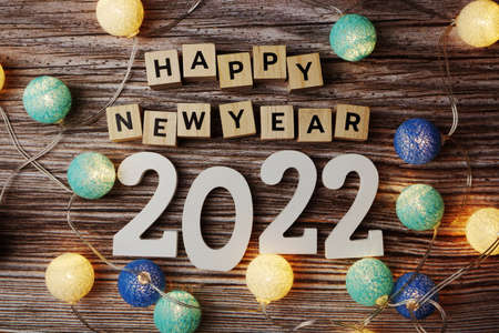 Happy New Year 2022 decorate with LED coton ball on wooden background