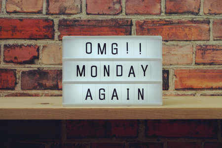 Monday Again word in light box on brick wall and wooden shelves background