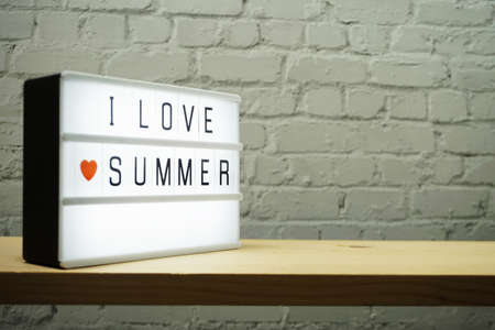 I Love Summer word in light box on white brick wall and wooden background