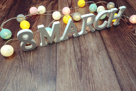 8 March Womens Day alphabet letters and LED cotton balls decoration on wooden background