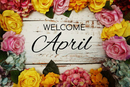 Welcome April text and Flowers Colorful Border Frame on wooden background