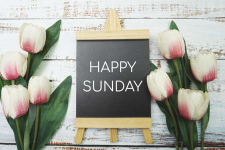 Happy Sunday text and Bouquet of tulips on white wooden background