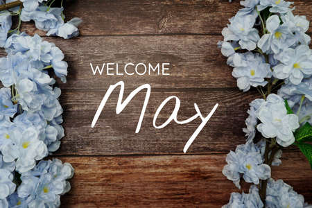 Welcome June text and blue flower decoration on wooden background