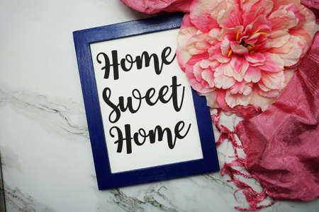 Home Sweet Home calligraphy and pink flower flat lay on marble background Фото со стока