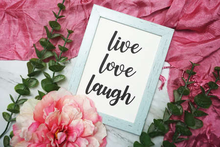 Live Love Laught written on blue frame with pink flower flat lay on marble background Фото со стока