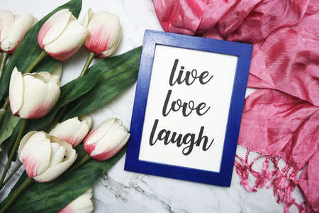 Live Love Laught written on blue frame with tulip flower flat lay on marble background Фото со стока