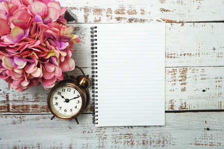 Notebook with blank pages withh alarm clock and floweron wooden background Фото со стока
