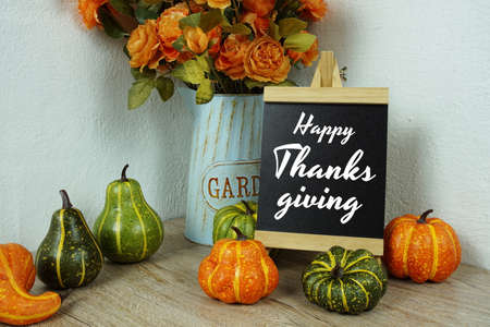 Happy Thanksgiving Day typography text with pumpkin decoration on wooden table Foto de archivo