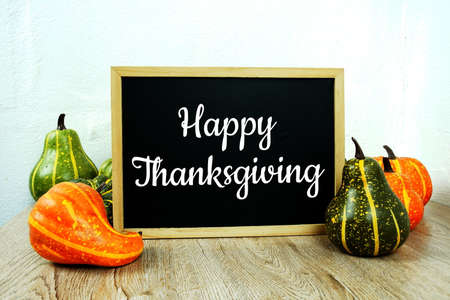 Happy Thanksgiving Day typography text with pumpkin decoration on wooden table