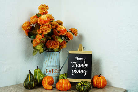 Happy Thanksgiving text in blue border frame with flower decoration on wooden background