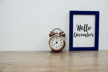 Hello December typography text with alarm clock on wooden table and white wall background