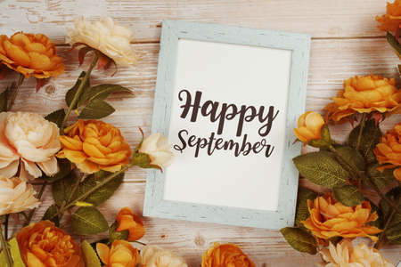 Happy September typography text with flower decoation on wooden background
