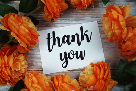 Thank you card with flower decoration on wooden background