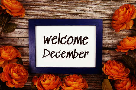 Welcome December text in blue border frame with flower decoration on wooden background