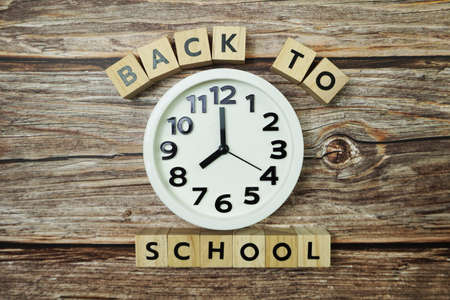 Back to School with clock on wooden background Фото со стока