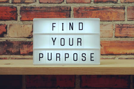 Find Your Purpose word in light box on brick wall and wooden shelves background