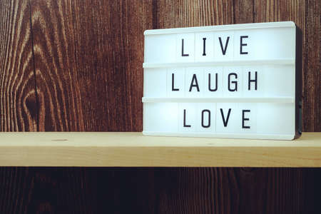 Live Laugh Love word in light box on wooden background