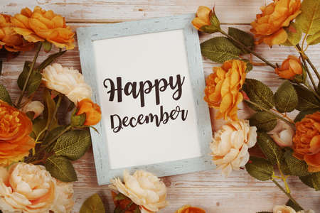 Happy December typography text with flower decoation on wooden background